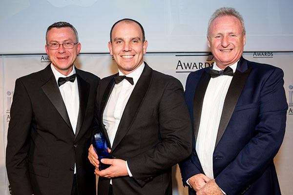 Zak McElvenny Group Compliance & Standards Manager is seen receiving the award on behalf of the company.